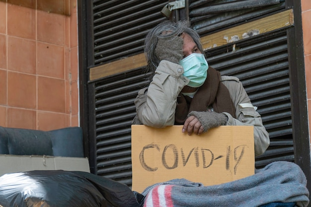 A homeless man carries a covid-19 sign, a problem of modern megacities.