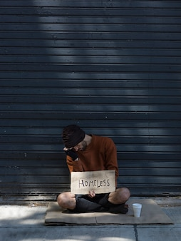 Homeless man hiding his face and asking for money long view