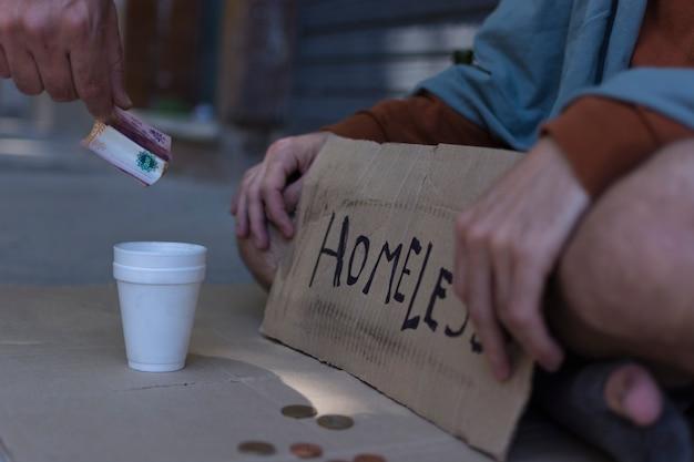 Бездомный человек с табличкой для попрошайничества