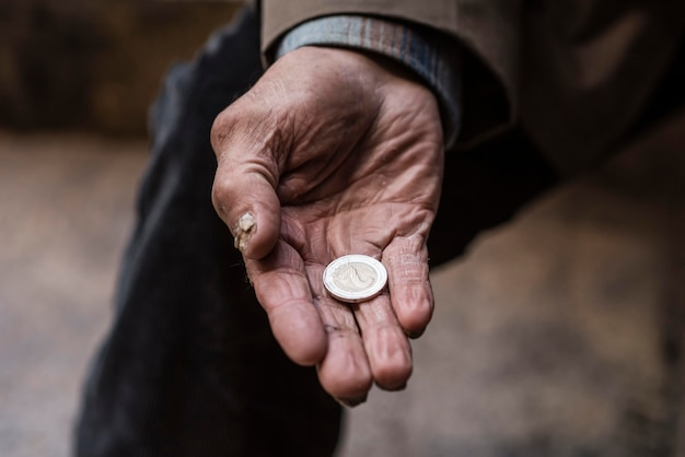 Homeless man holding coin in his hand