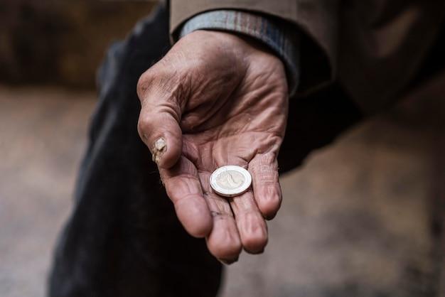 Бездомный мужчина держит в руке монету
