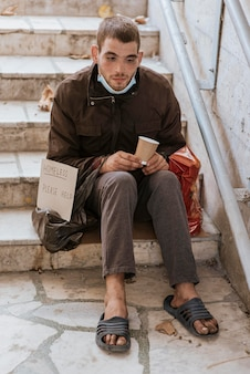 Homeless man holding cup and help sign on stairs