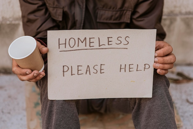 Homeless man holding cup and help sign