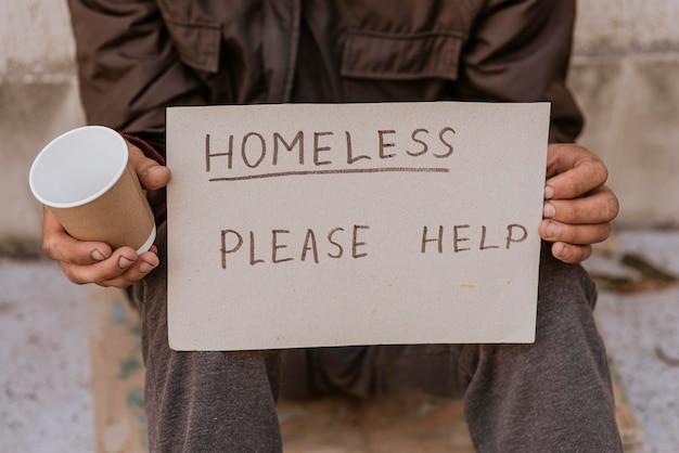Uomo senza casa che tiene tazza e segno di aiuto