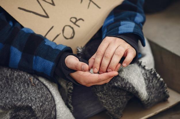 Бездомный мужчина в сумасшедшей одежде осеннего города