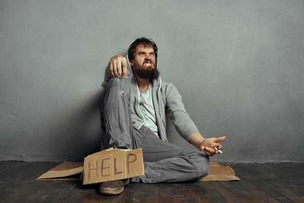 汚れた服を着たホームレスの男性が路上でお金を懇願する