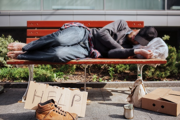 Homeless man is lying on bench and sleeping. hee is tired and exhausted. there is a bag with stuff underneath his head. there is a help cardboard and a metal cup with money on the ground.
