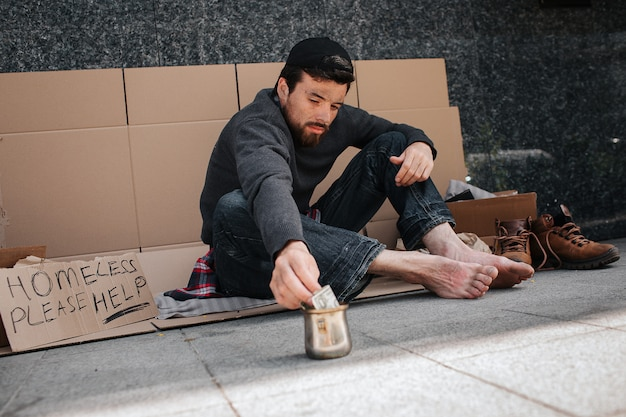Homeless man is sitting on the cardboard outside and reaching metal cup with his hand. he is reaching a dollar. there is a sign says homeless please help. guy wants to take that money.