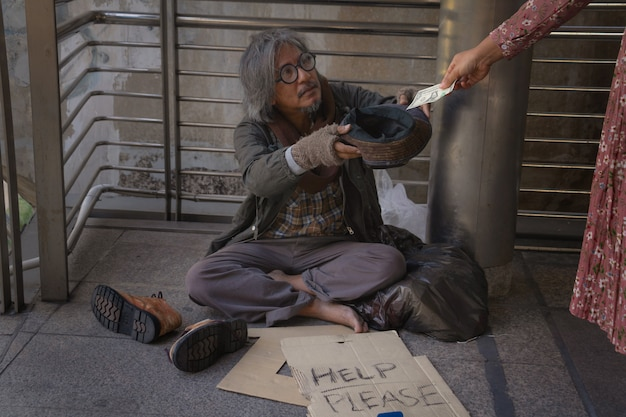 Homeless man is sitting down on walkway in town. he is holding hat and receive dollar.