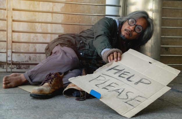 "A homeless man is sitting on walkway in town. he is show label ""help please ""word."