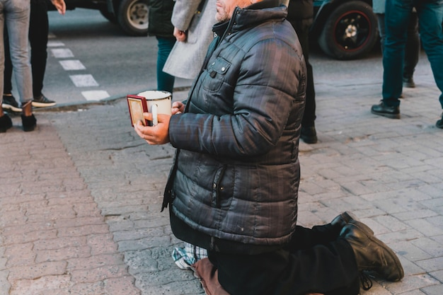Homeless man kneels on the street around the people and asks to give money into cup in him hands.