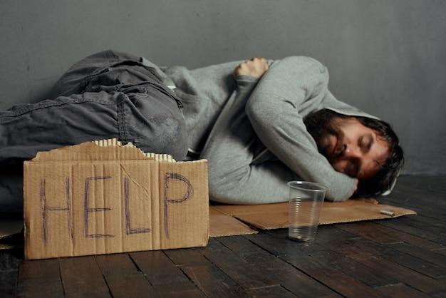 노숙자 우울증에 도움이 되는 표지판을 들고 바닥에 누워 있는 노숙자