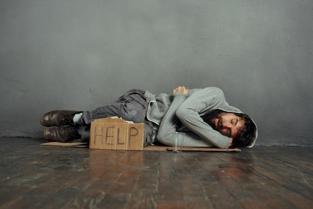 看板を持って床に横たわっているホームレスの男性は、ホームレスのうつ病を助けます