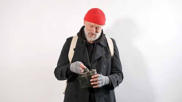 Homeless man, an old man with a gray beard in a hat smiling holding in his hand financial aid, dollars, isolated white background