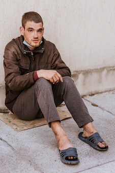 Бездомный на улице с медицинской маской
