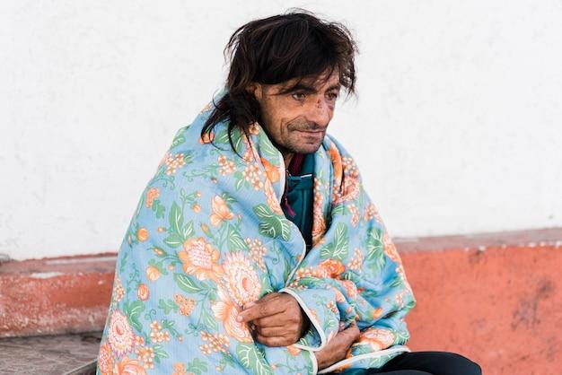 毛布の下で外のホームレスの男性