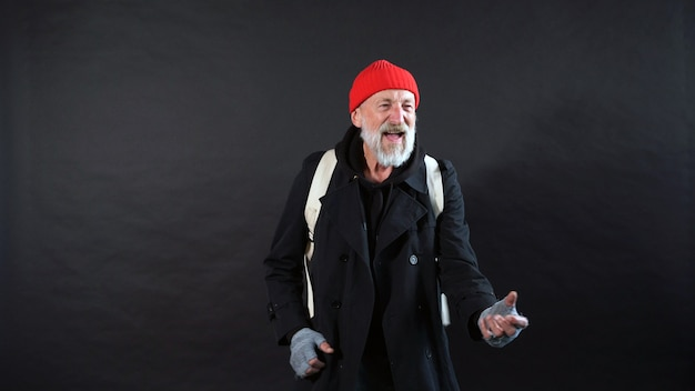 Homeless man, a pensioner, an old man with a gray beard in a coat and a red hat on an isolated dark background