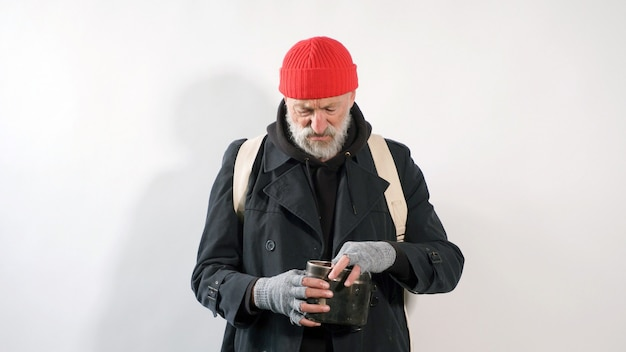 Homeless man, a pensioner, an old man with a gray beard in a coat and a red hat on an isolated white background