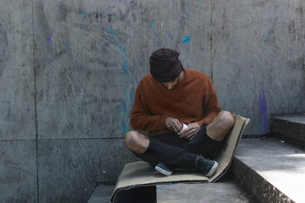 Homeless man sitting on a cardboard outdoors