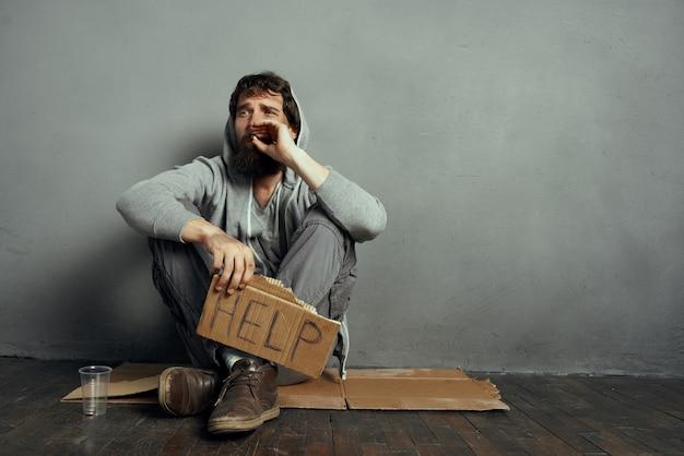 看板を持って床に座っているホームレスの男性は、タバコのライフスタイルを吸うのに役立ちます。高品質の写真