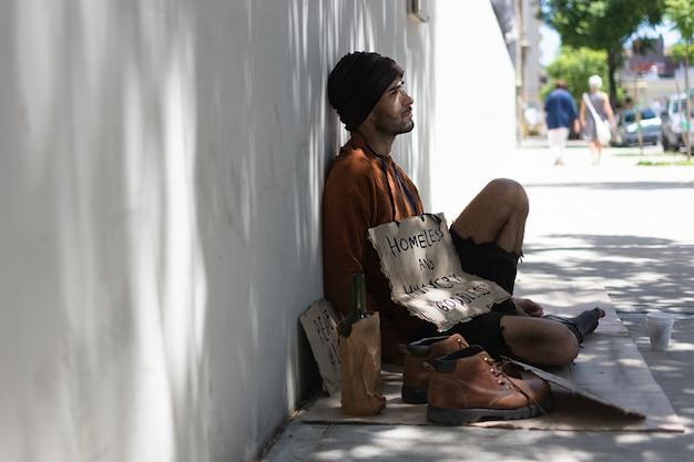 Бездомный мужчина сидит на полу на улице