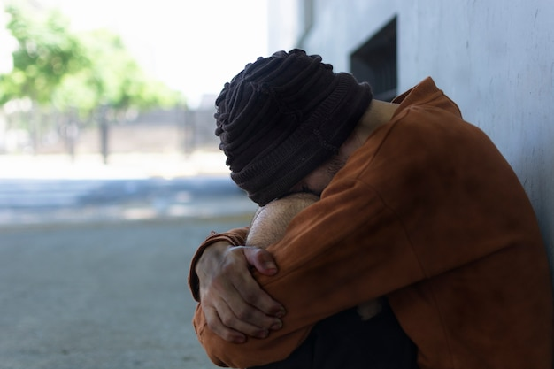 路上で座っているホームレスの男性