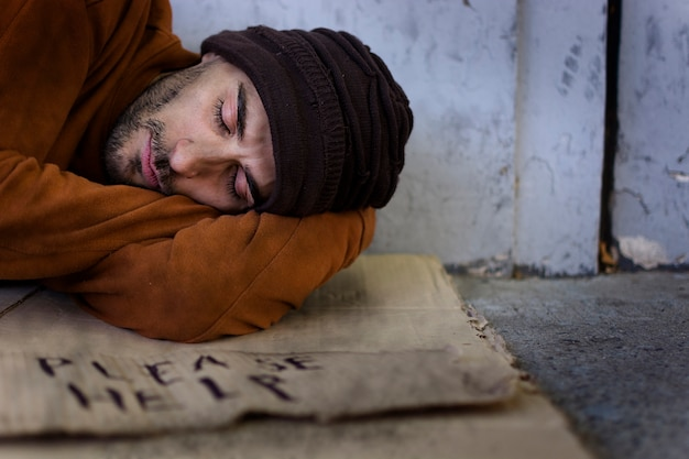 Homeless man sleeping on cardboard
