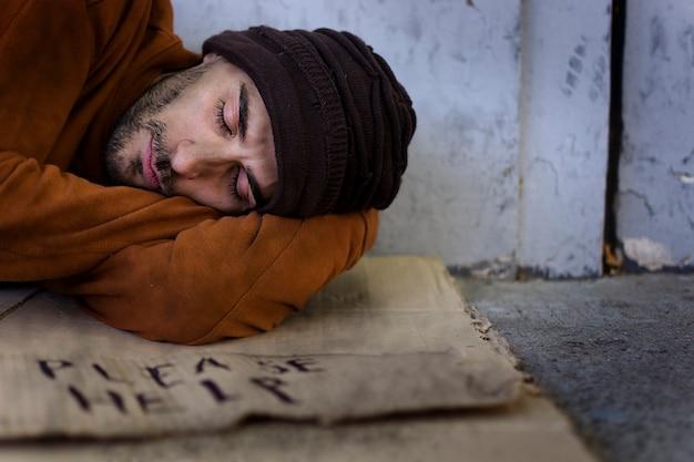 Бездомный человек спит на картоне