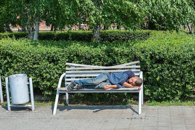A homeless man sleeps on a bench in a park
