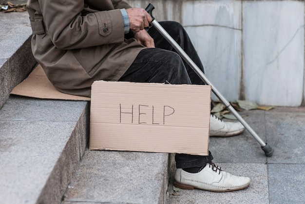 Homeless man on stairs with cane and help sign