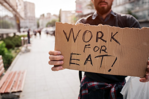 Homeless man standing outside and holding a cardboard which says work for eat