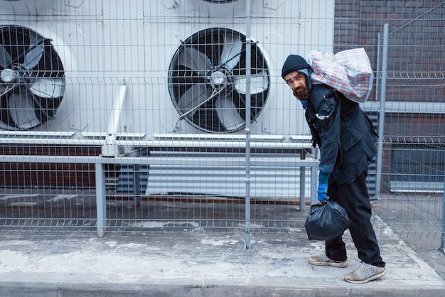 Homeless man with bag on city street.
