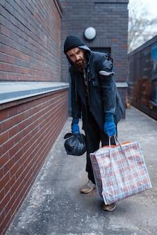 街の通りにバッグを持つホームレスの男性。