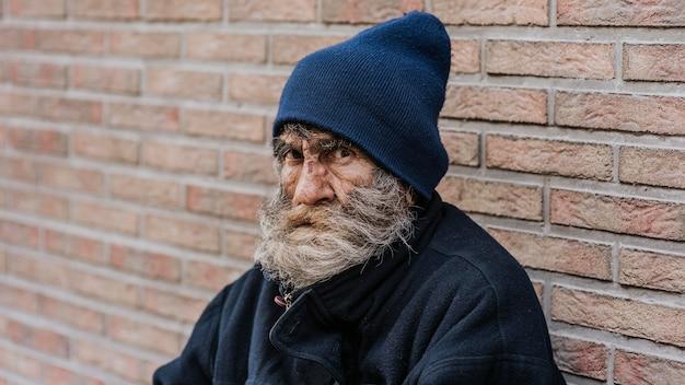 Uomo senza casa con la barba davanti al muro