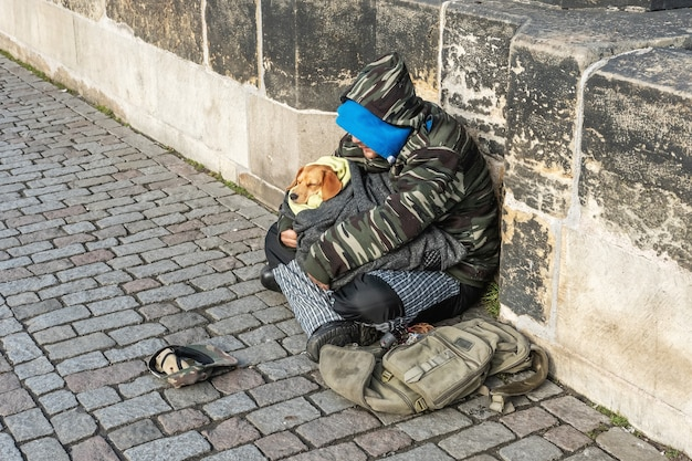 Homeless man with a dog sitting on the charles bridge begging for help and money.