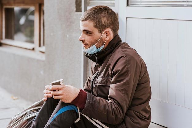 外にビニール袋とカップを持つホームレスの男性