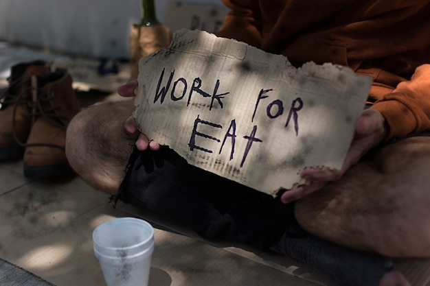Homeless man with work for eat sign