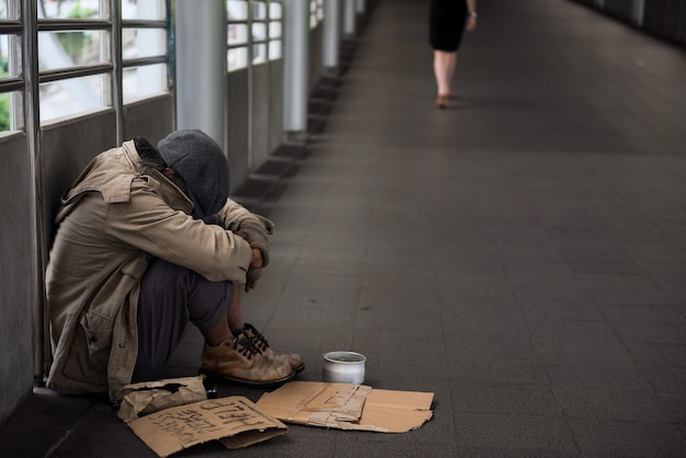 Homeless old man or beggar head down and sit with donated bowl and help sign banner.