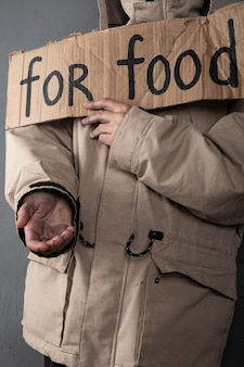 Homeless person asking for food, help sign.