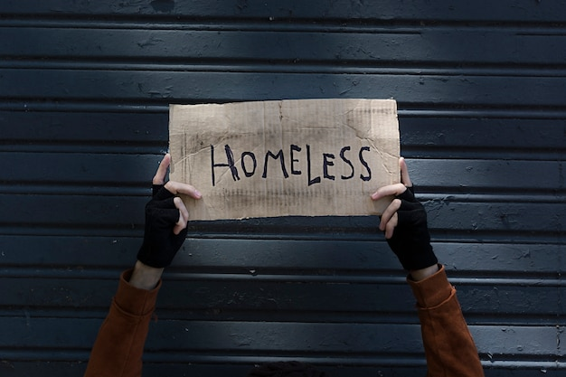 Homeless sign held by a beggar hands
