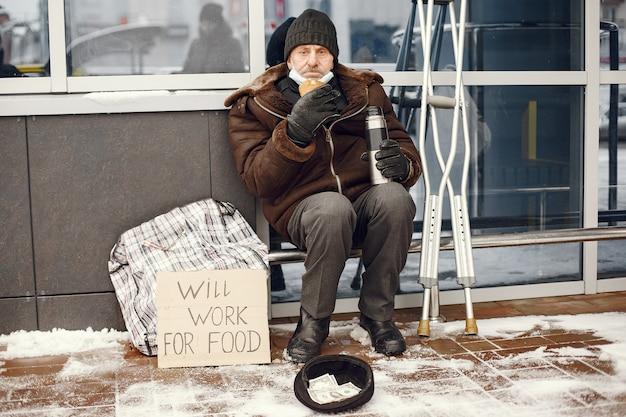 건물 근처에 노숙자 앉아.