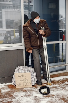 Homeless standing near building.