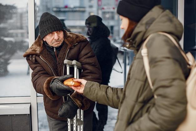 Senzatetto in una città invernale. uomo che chiede cibo.