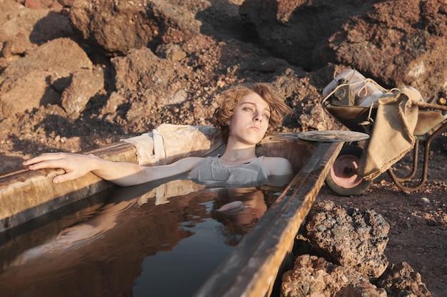 더러운 물에 누워 야외에서 목욕하는 노숙자 여성