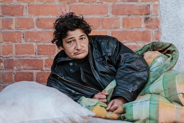 Бездомная женщина под одеялом на открытом воздухе