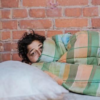 屋外で毛布と枕を持つホームレスの女性