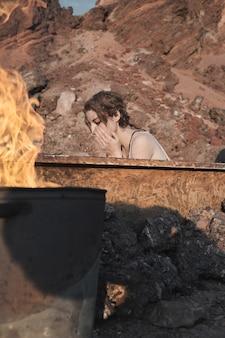 노숙자 젊은 여성이 욕조에 앉아 야외에서 불 근처에서 얼굴을 씻고 있다