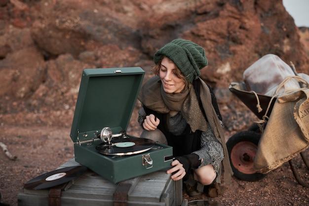 야외에서 음악을 듣기 위해 축음기를 켜는 노숙자 젊은 여성