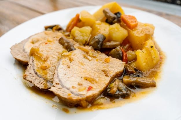 Домашняя свиная корейка с картофелем и грибами в соусе в кастрюле длительного или медленного приготовления. концепция домашнего питания, здоровая и натуральная пища, медленное приготовление. нормальный вид.