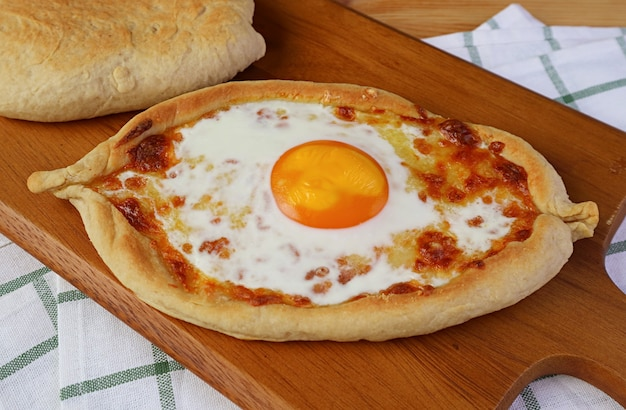 Домашний аджарский хачапури, грузинский хлеб с сыром и свежими яйцами